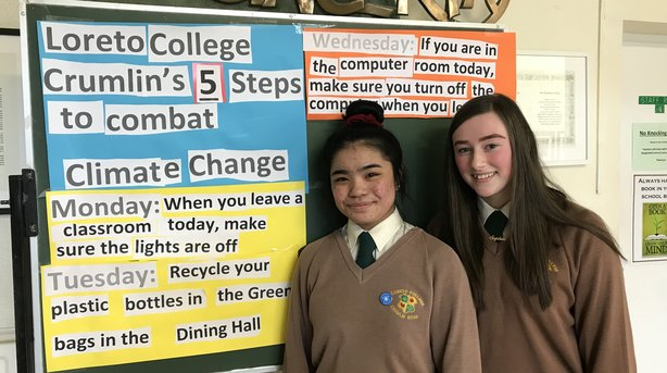 Keiffer Cortez and Sophie O'Connor in front of 5 Easy steps to combat climate change display in our school reception area.
